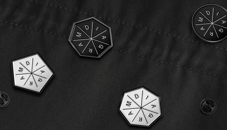 Seven-sided black and white enamel pins featuring the Diagram logo on a black fabric background