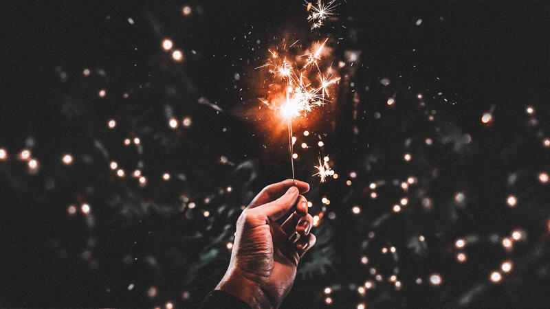 A hand holding a lit sparkler on a black background making a visual allusion to the shape of the Diagram logo