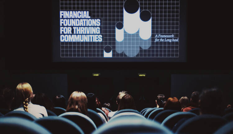 Audience in an auditorium with GFOA graphics visible on a stage screen