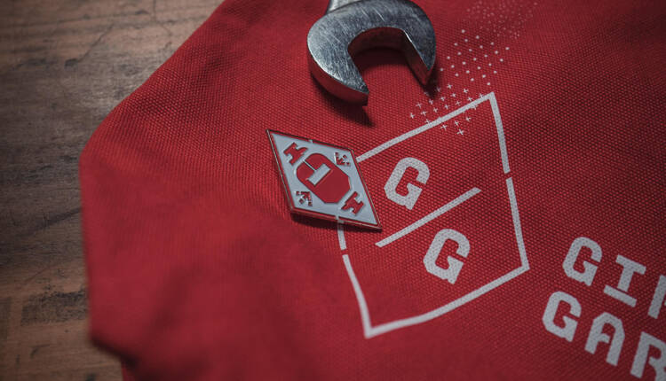 Logo with enamel pin and wrench laying on a red canvas tote bag