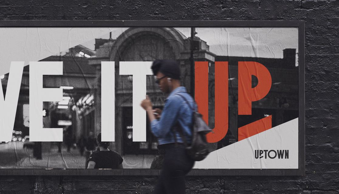 "Woman walking in front of billboard featuring Uptown logo and campaign message ""Live it Up"""