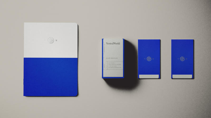 Vested World notebook and business cards featuring logo and brand colors
