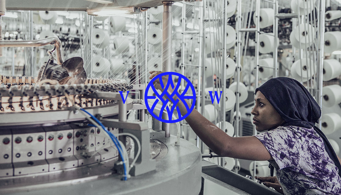 Vested world monogram logo on top of a photograph of a woman working in a factory
