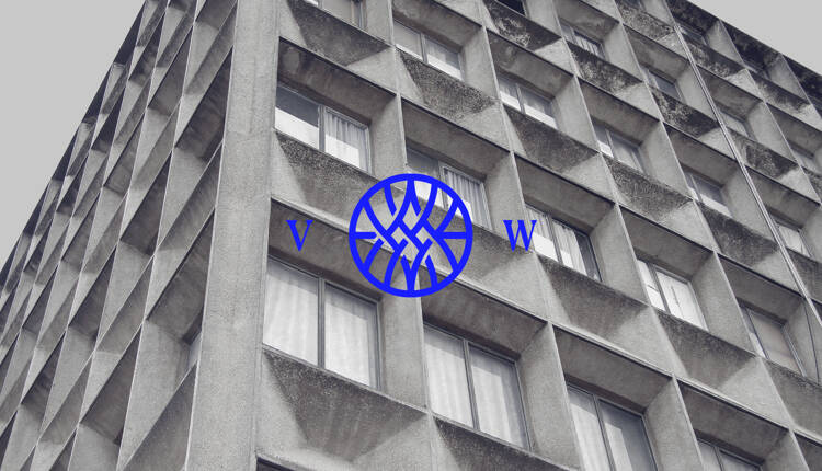 Vested World monogram logo on top of a photograph of a highrise building